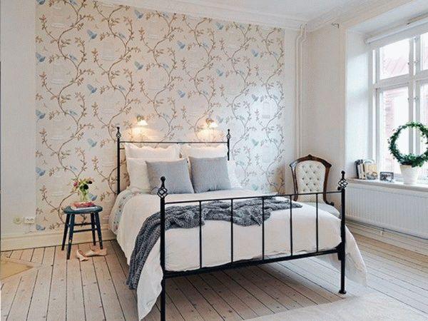Стену у изголовья кровати можно оклеить обоями другого цвета или фактуры