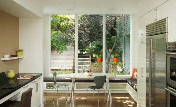 Стол возле панорамного окна позволит наслаждаться видом улицы во время еды или приготовления пищи
