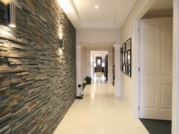 Чтобы акцентировать внимание на стене, отделанной камнем, централизованное освещение лучше заменить точечным