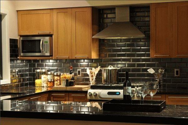 Черная плитка в интерьере кухни встречается достаточно редко