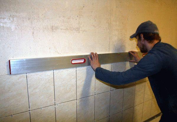 При укладке плитки на стену каждый элемент обязательно проверяется строительным уровнем