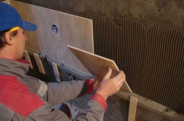 Работы с плиткой начинаются со второго ряда, для этого устанавливают деревянную рейку