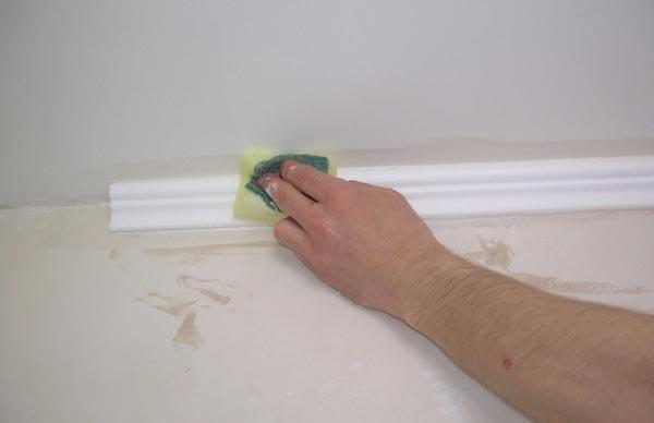 После легкого нажатия на плинтус может выступить немного клея, который сразу убираются с помощью губки
