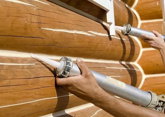Перед облицовкой деревянного дома все щели и трещины нужно заделать специальной шпаклевкой или герметиком