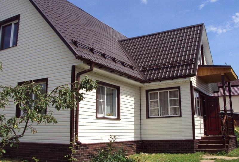 Белый или бежевый сайдинг будет смотреться более выразительным, если окна и двери будут выделены темными элементами
