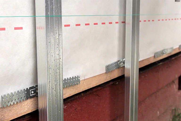 Для выравнивания стоек металлического каркаса используется шнур, который натягивается между угловыми профилями