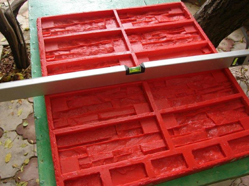 Чтобы обратная сторона у всех плиток была ровная, форму кладут на прямую поверхность и с помощью уровня проверяют наличие отклонения по горизонтали